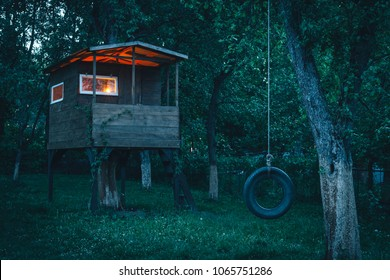 House on tree in evening garden. Childhood concept