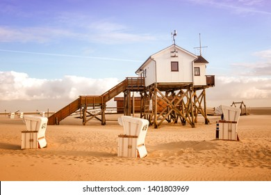 house on wooden stakes on the beach and wicker beach chairs on sunny day