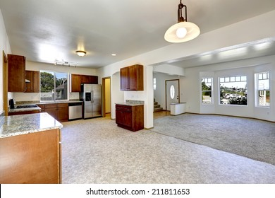 House with open floor plan. Empty living and kitchen room with granite tops ans steel appliances