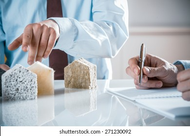 House owner and architect discussing a choice of insulation materials pointing to one as the architect draws up the contract