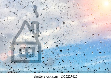 House painted on misted glass. Window glass with raindrops against a blue sky and sun. Imitation of children's drawings.