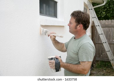 A house painter edging around a window with a brush.  Room for text.