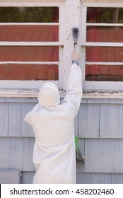 A house painter in a hazmat suit scrapes off dangerous lead paint from a window sill.
