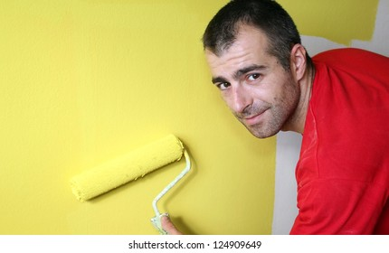 House Painter. Man, painting a wall with yellow paint and a paint roller. Selective focus.
