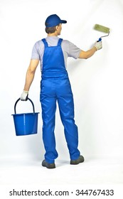 house painter is painting white wall, Back view from behind Young full length man in blue overalls with painting tools Empty copy space for inscription