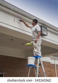 House painter rolling new paint on soffit