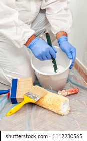 House painter at work mixes paint and water in a container