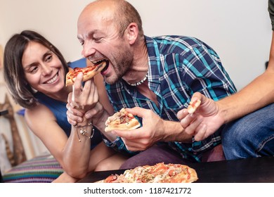 House party. Friends eating and having fun. Man playfully takes a slice of pizza from the smiling woman.