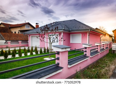 house with pink facade, pvc door and window and iron fence on wall