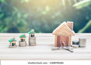 House placed on coins. houses, keys placed on a wooden table.  planning savings money of coins to buy a home concept for property ladder, mortgage, real estate investment, saving  for a buy house.