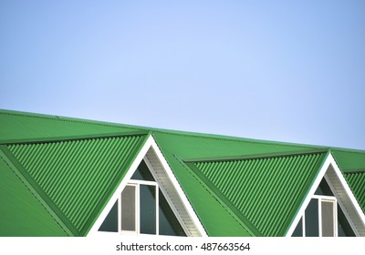 The house with plastic windows and a green roof of corrugated sheet. Roofing of metal profile wavy shape on the house with plastic windows.