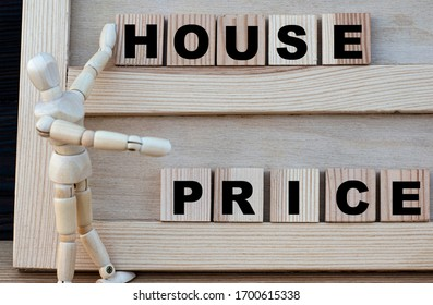 HOUSE, PRISE words are written on the board. Nearby is a wooden man. Business concept. - Shutterstock ID 1700615338