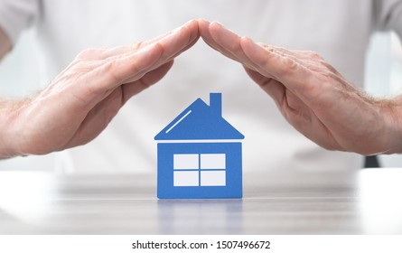 House protected by hands - Concept of home insurance