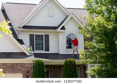 House proud man cleaning the upper floor windows with a squeegee as he stands on the patio roof of an upmarket home