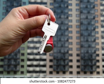 House purchase. Real estate agent holding house key on background of new buildings. Moving home or renting property