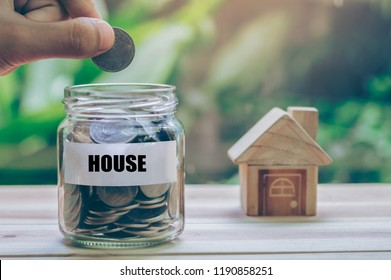 "House put on the wood. Men's hand is putting coin into jar with the words ""house""  planning savings money of coins to buy a home concept for property, mortgage and real estate investment for a house."