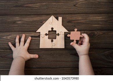 house of puzzles, hands, missing detail on a wooden background. logical game.