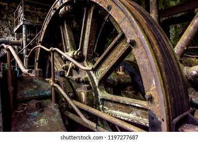 House of railway machinery with pulleys and gears in old and rusty cast metal rails deactivated