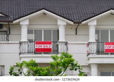 The house or real estate for sale with the board suspended on the fence of balcony. About the housing market decline, economic recession, or financial crisis resulted from subprime mortgage.