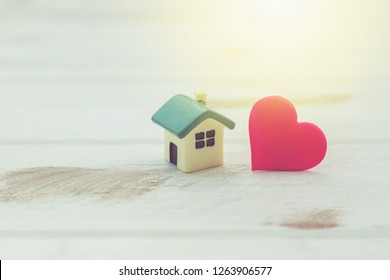 House with a red heart on white wooden background