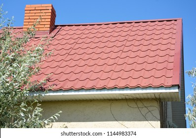 House with red metal roof and white plastic soffit boards. Roofing construction.