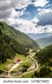 A house with red roof, next to a winding road in a mountain pass in the Carpathian Mountains, Transfagarasan (Romania).