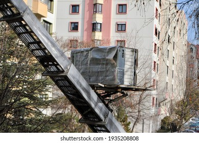 House removal with hydraulic ladder truck. Moving lift carrying furniture up in a residential district . Selective focus.