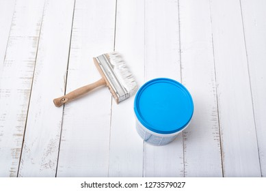 House renovation concept. Brush and a paint bucket on a background of white, shabby wooden planks