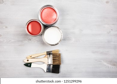 House renovation, paint cans and colored brushes on white wooden background. Living Coral Color of the year 2019.