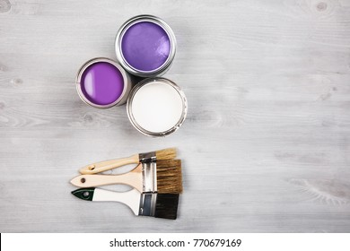 House renovation, paint cans and colored brushes on white wooden background. Ultra Violet color of paint.