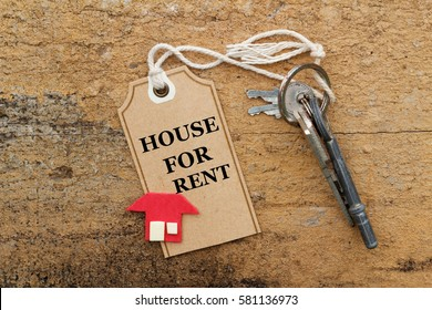 House for rent concept. Rusty keys and a replica of a house on old wooden background with words House For Rent.