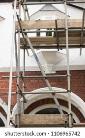 House repair. It`s a temporary structure on the outside of a building. Metal scaffolding poles with wooden planks attach to a building. Construction work.