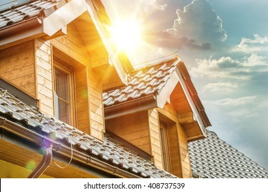 House Roof and Attic Windows Closeup. Sunny Day. Housing and Construction Concept Photo.