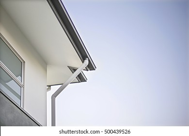 House roof and ceiling with drain pipe  fixed to the white walls including a glass  window with a aluminum bars, the blue sky is from the right side with no clouds, walls are painted in white color