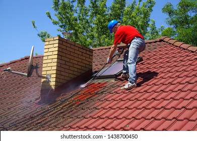House roof cleaning with pressure tool. Worker on top of building washing tile with professional equipment. Moss removing with water.