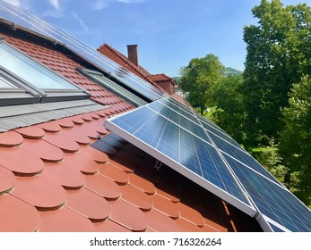 house roof with solar panels on top with green trees and meadow against great blue sky