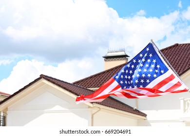 House roof and waving USA flag on blue sky background