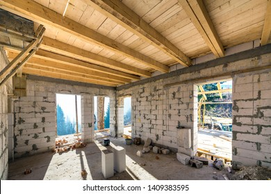 House room interior under construction and renovation. Energy saving walls of hollow foam insulation blocks, wooden ceiling beams and roof frame.