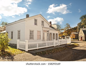 house in a rural town with white picket fence
