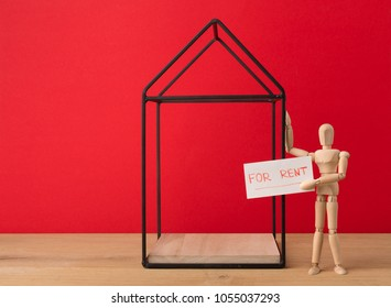 House for sale on red background. Wooden mannequin holding advertisement board. Real estate and buying from owner concept, copy space