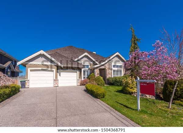 House for sale in Vancouver, Canada. Real estate sign in front of a house.