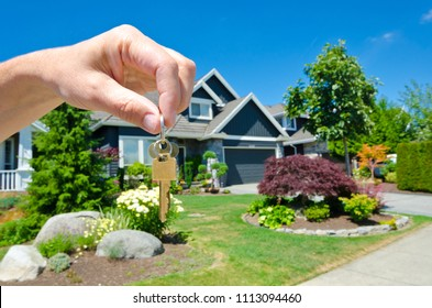 House for sale.Hand holding the keys for a big custom made luxury house.