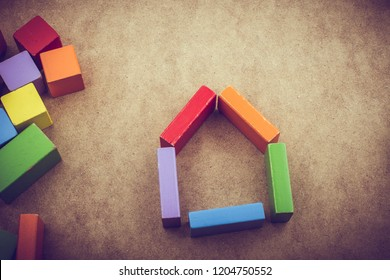 House shape formed out of building blocks on a brown background