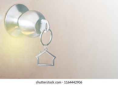 House shape key chain hanging on door knob. concept of buying new house and home safety