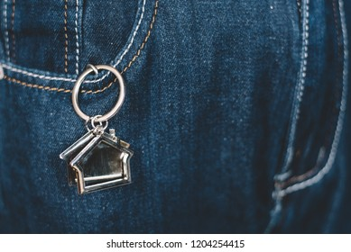 House shape keychain or key holder in a jeans pocket. Concept of own a house and home financing