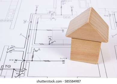 House shape made of wooden blocks lying on electrical construction drawings, concept of building home
