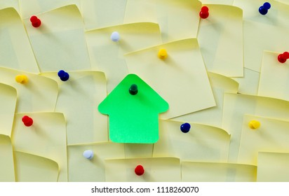 House shape note sticker on cork board.