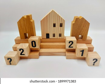 House shaped blocks staged on wooden steps to present housing market analysis and comparison between 2020 and 2021