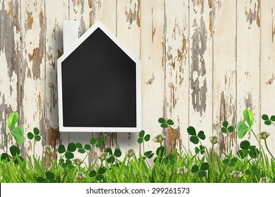 House shaped chalkboard on wooden plank background
