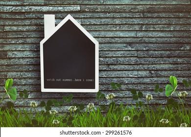 House shaped chalkboard on wooden plank background